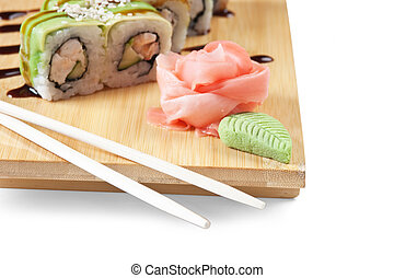 Asian food sushi on wooden plate isolated on white background