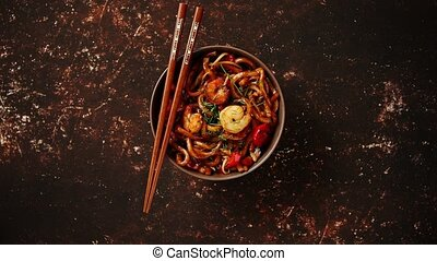 Traditional asian udon stir-fry noodles with shrimp in bowl...