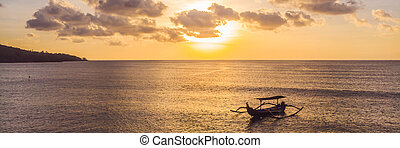 Traditional Balinese boat Jukung at Jimbaran beach at sunset in Bali, Indonesia Photo from the drone BANNER, long format