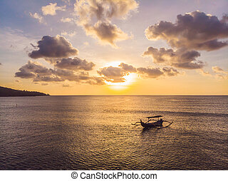 Traditional Balinese boat Jukung at Jimbaran beach at sunset in Bali, Indonesia Photo from the drone