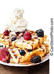 Traditional Belgian waffles with ice cream and berry fruits on wooden background, homemade healthy breakfast