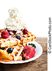 Traditional Belgian waffles with ice cream and fruits on wooden board, isolated