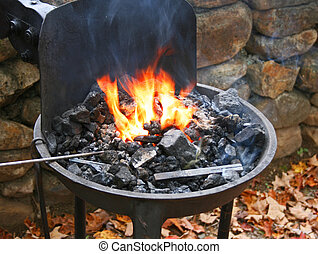 Traditional blacksmith's portable forge with flaming coals