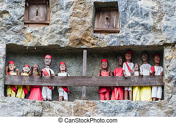 Lemo (Tana Toraja, South Sulawesi, Indonesia), famous burial site with coffins placed in caves carved into the rock, guarded by balconies of dressed wooden statues, images of the dead persons (called tau tau in local language).