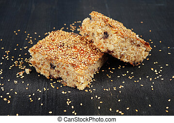 Traditional cake with sesame seeds, nuts and chocolate on black wooden background
