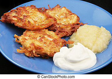 Potato latkes for Hanukkah, served with sour cream and applesauce .