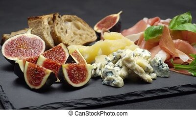 traditional cheese and meat plate wth parma, parmesan and figs