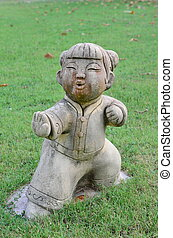 Traditional child Chinese style statue on the grass in garden