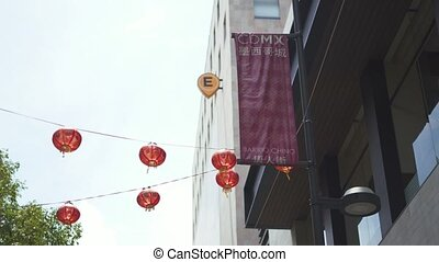 4k Circling view of traditional Chinese lamps and banners hanging from cables and lampposts