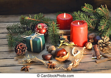 traditional christmas decoration on wooden table with candles and gift box