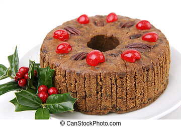 A beautiful Christmas fruitcake garnished with cherries and holly berries. White background.