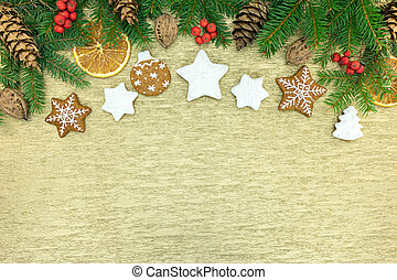 traditional christmas gingerbread cookies and fir-tree branches with decorations on gold wrapping paper
