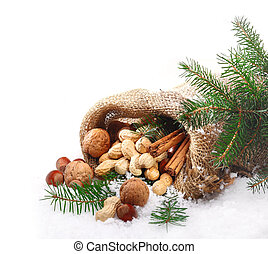 An assortment of traditional Christmas nuts spilling out of a hessian bag onto fresh winter snow with pine foliage and copyspace for your seasonal greeting