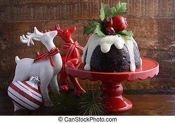 Traditional Christmas Plum Pudding on red cake stand with ...