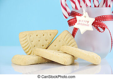 Traditional Christmas shortbread triangle shape cookies with jar of candy canes against a pale blue and white background.