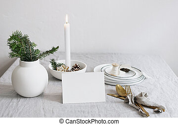 Traditional Christmas table place setting. Golden cutlery, fir tree branches in vase, plates and burning candle in ceramic candleholder on linen table cloth. Holidays background. Place card mockup