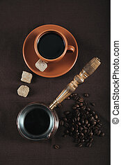 traditional coffee turk and ceramic cup with brown sugar cubes and coffee grains on brown cloth