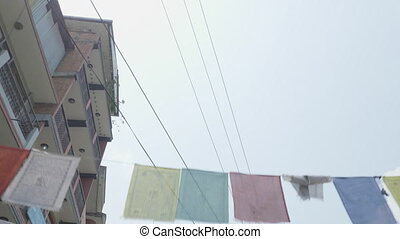 Traditional colorful buddhism prayer flags over over street...