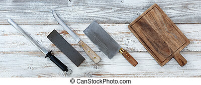 Traditional cooking knives with sharpening tools on white vintage wooden planks