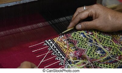 Traditional Cotton Woven. - Hands of woman weaving sarong...