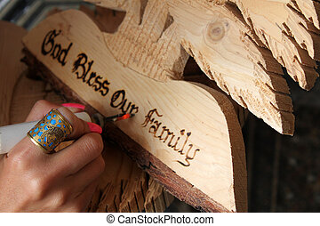 A Lebanese woman carving God bless our family on a wooden cedar shape in a Lebanese traditional craft shop.