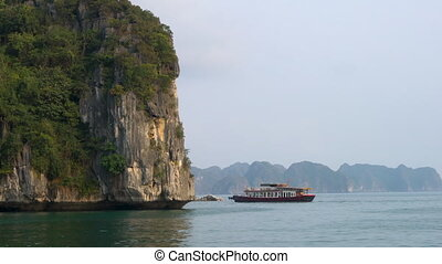 Traditional cruise boat sailing through the limestone islands in UNESCO World Heritage site, Ha Long Bay, Cat Ba National Park, Vietnam