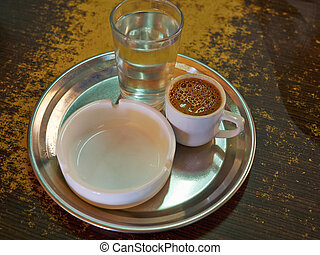 Traditional Cypriot Greek coffee served with cold water in a...