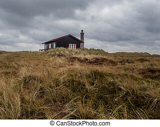 Traditional Danish wooden cottage in front of a lighthouse