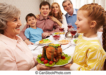 Traditional dish - Senior woman with cooked turkey looking...