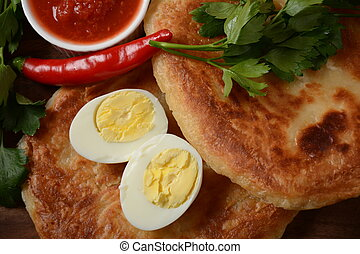 Traditional dishes of Israeli and Middle Eastern cuisine - Malawach with hard boiled eggs and tomatoes.  Malawach or malawah: traditional fried bread of Yemenite Jews