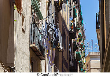 Traditional drying clothes of the local people in the historic famous Gothic quarter of Barcelona in sunny day. Spain.