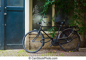 Traditional dutch bicycle parked at the front door in Amsterdam