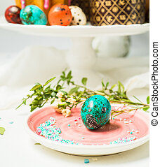 Traditional Easter colored eggs, green leaves on white background