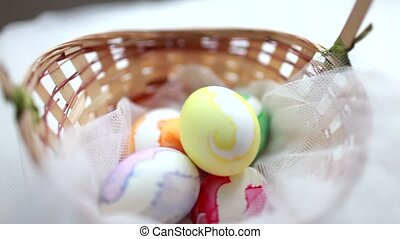 Traditional easter colorful eggs in a plate. A candle is burning nearby and a plate of sweets lies.