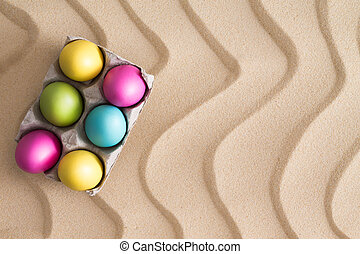 Traditional Easter Egg hunt at the beach with a box of...