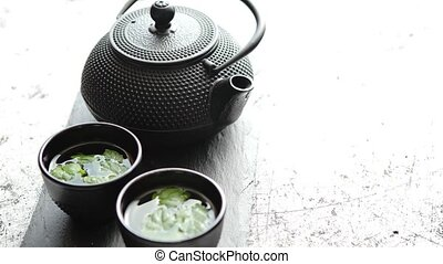 Traditional eastern metal teapot and iron cups with mint tea...