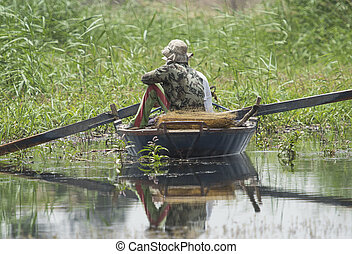 Traditional egyptian bedouin fisherman on river by reeds