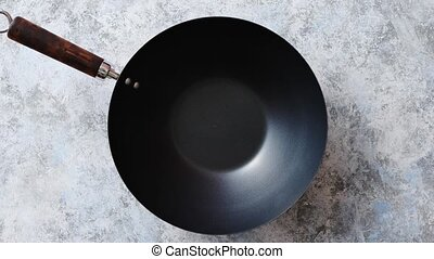 Traditional empty black iron wok pan placed on stone...