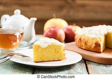 Traditional English cake with apples and whipped cream served with tea on blue wooden background