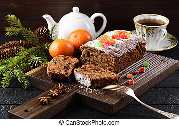 Traditional English fruit cake with candied fruits served with black tea, clementines and fir branch on oak board