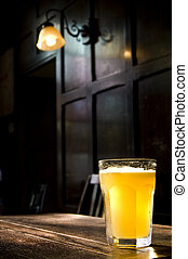 Traditional English Pub - A lone beer glass in a darkened ...