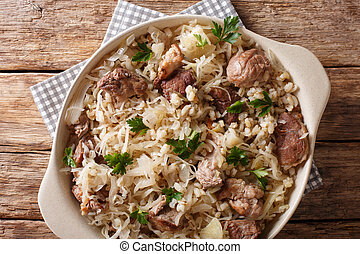Traditional Estonian festive dish of pork, barley and sauerkraut closeup on the table. Horizontal top view