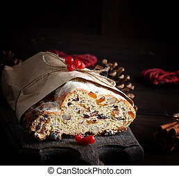 traditional European Stollen cake with nuts and candied fruit wrapped in a brown piece