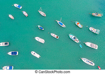 Traditional eyed colorful boats in the harbor of Mediterranean fishing village, aerial view Marsaxlokk, Malta.