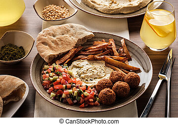 Traditional falafel balls with salad and hummus on a plate