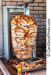 Traditional fast food doner kebab meat on a rotary grill. Shawarma is one of the most popular fast food