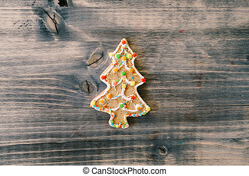 Traditional festive gingerbread cookies in the shape of a Christmas tree on a wooden board.