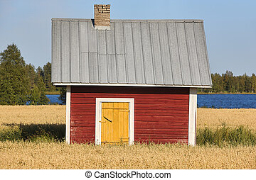 Traditional finnish red wooden farm in the countryside.