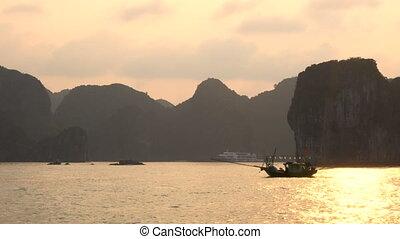 Traditional fishing boat sailing at sunset in Ha Long Bay, Cat Ba National Park, Vietnam