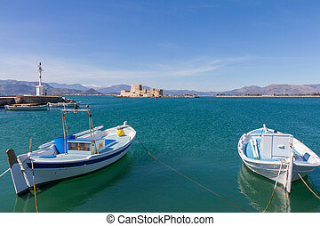Traditional Wooden Fishing Boats, Lightouse and Bourtzi Fortress in the background in Nafplion, Greece